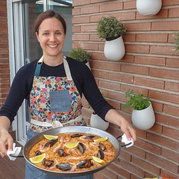 Woman holding a large pan of seafood and chorizo paella.