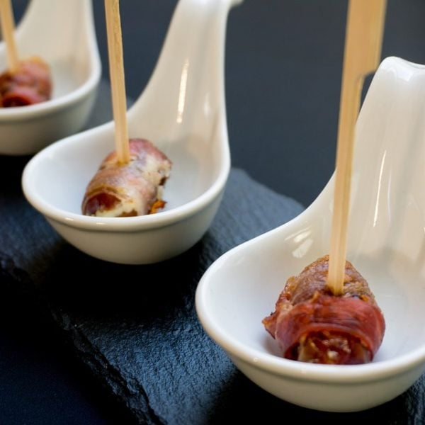 bacon wrapped dates pintxos on a counter