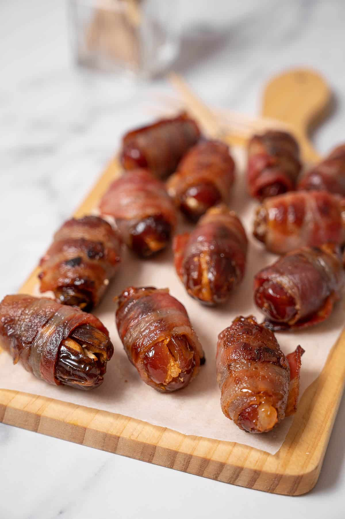 Bacon wrapped dates on a wooden platter.