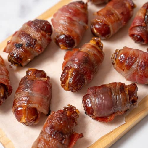 Stuffed Bacon wrapped dates served on a cutting board