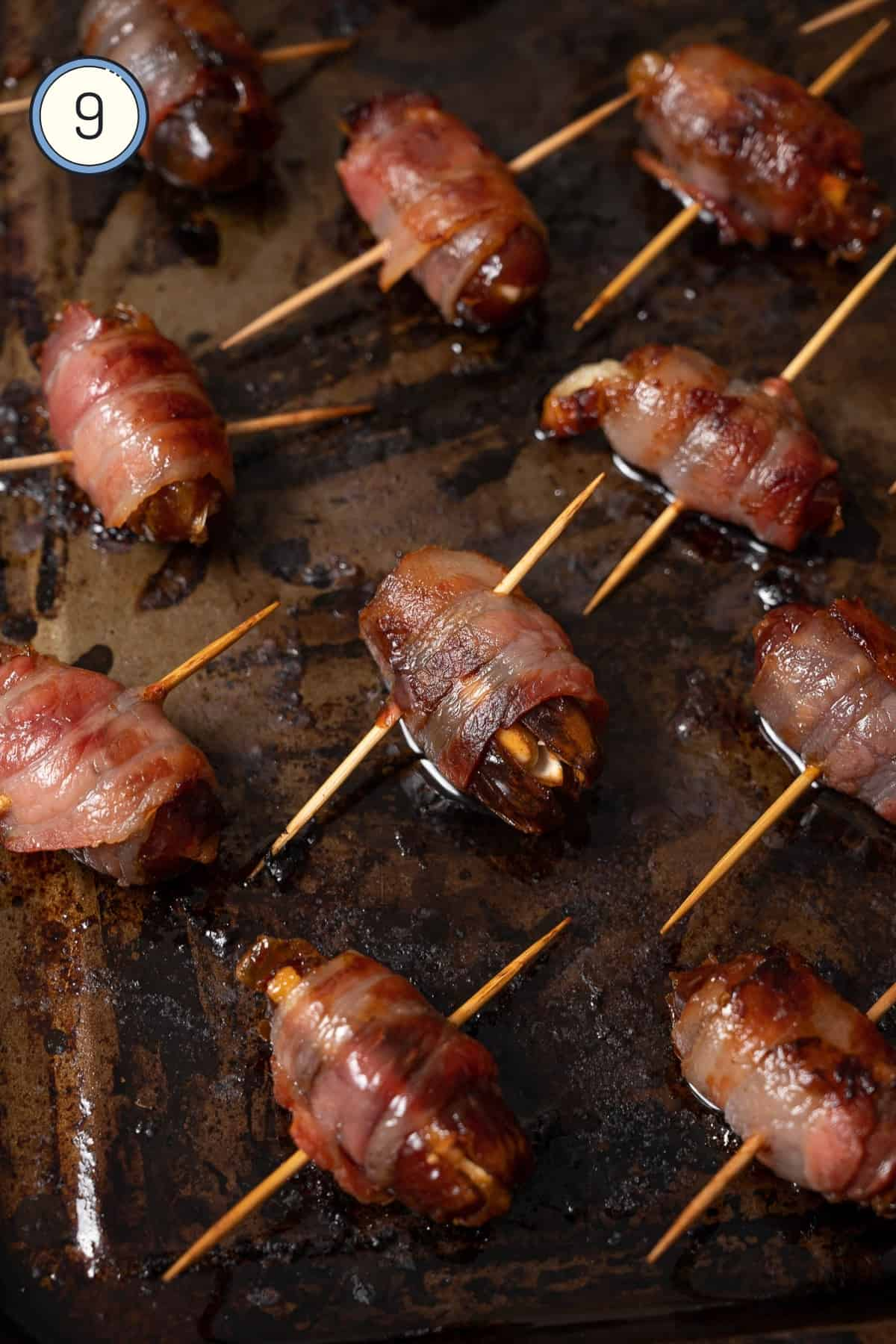 Cooked bacon wrapped dates on a baking tray.