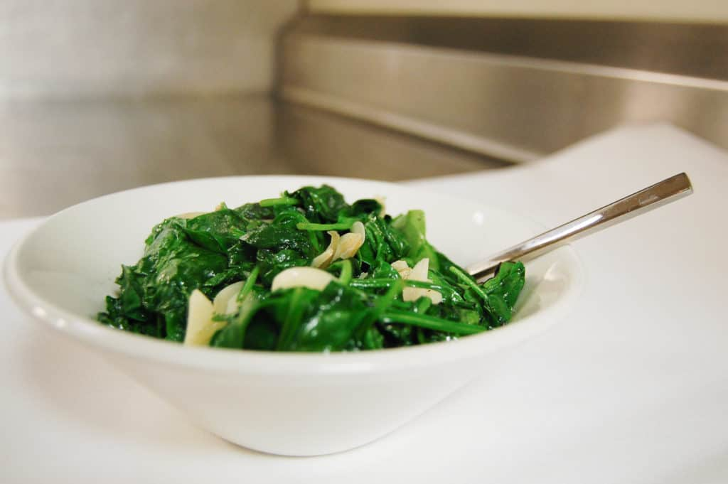 Sauteed spinach and garlic in a white bowl.