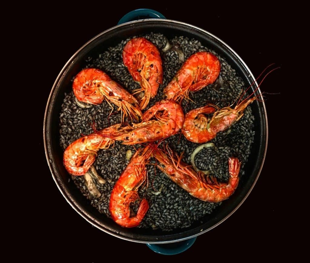 Overhead shot of black paella with bright red prawns