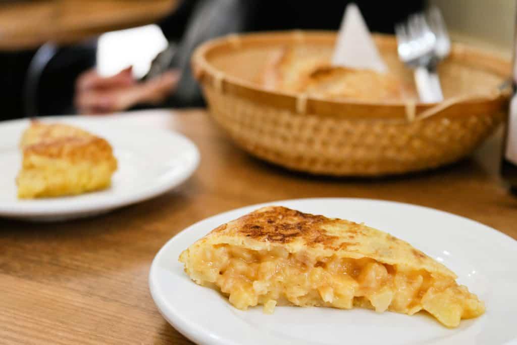 Slices of potato omelet on white plates