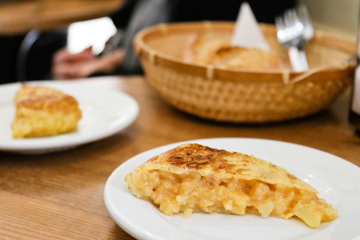 Slice of Spanish tortilla on a white plate in the foreground. Another slice and a bread basket in the background.