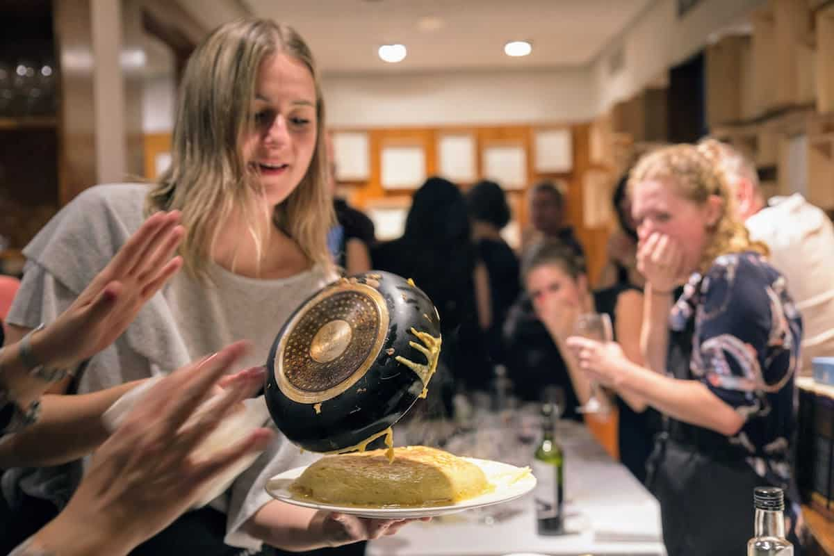 Young woman flipping a Spanish tortilla from a frying pan onto a white plate.