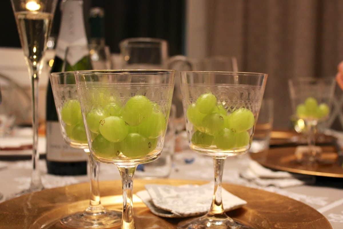 Several clear glasses filled with 12 white grapes each.