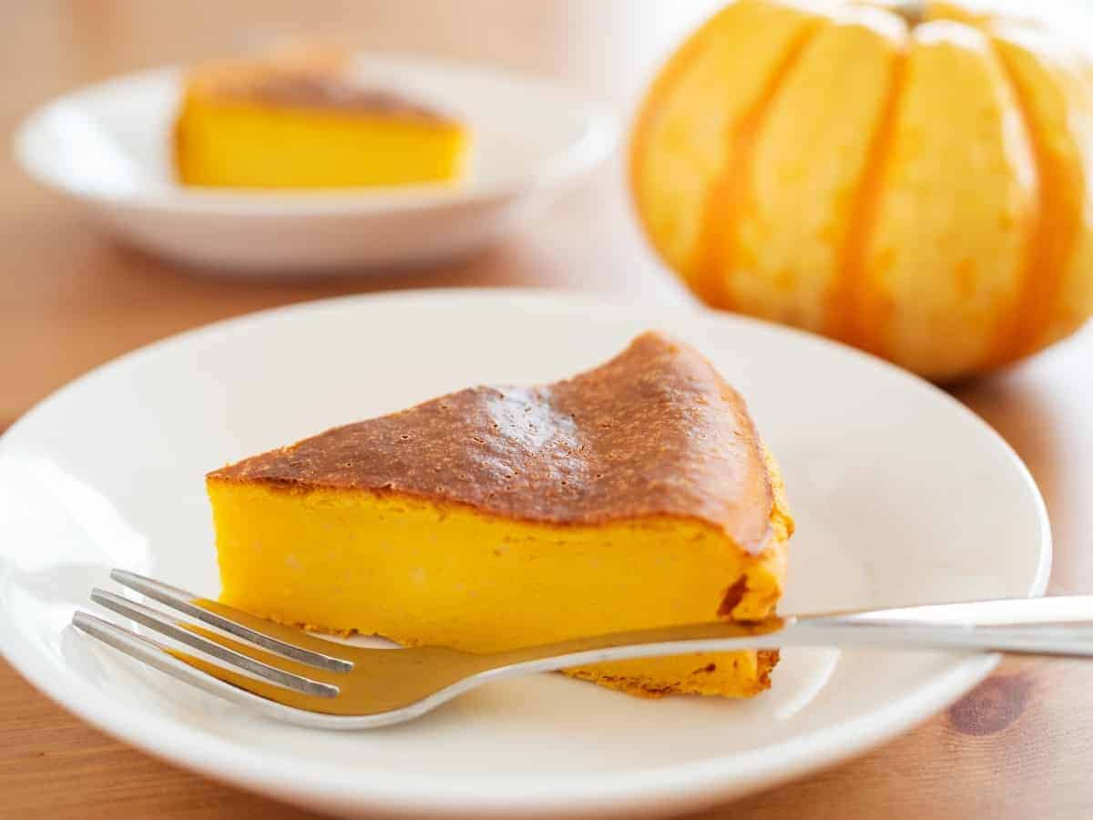 Slice of crustless pumpkin cheesecake on a white plate with a metal fork