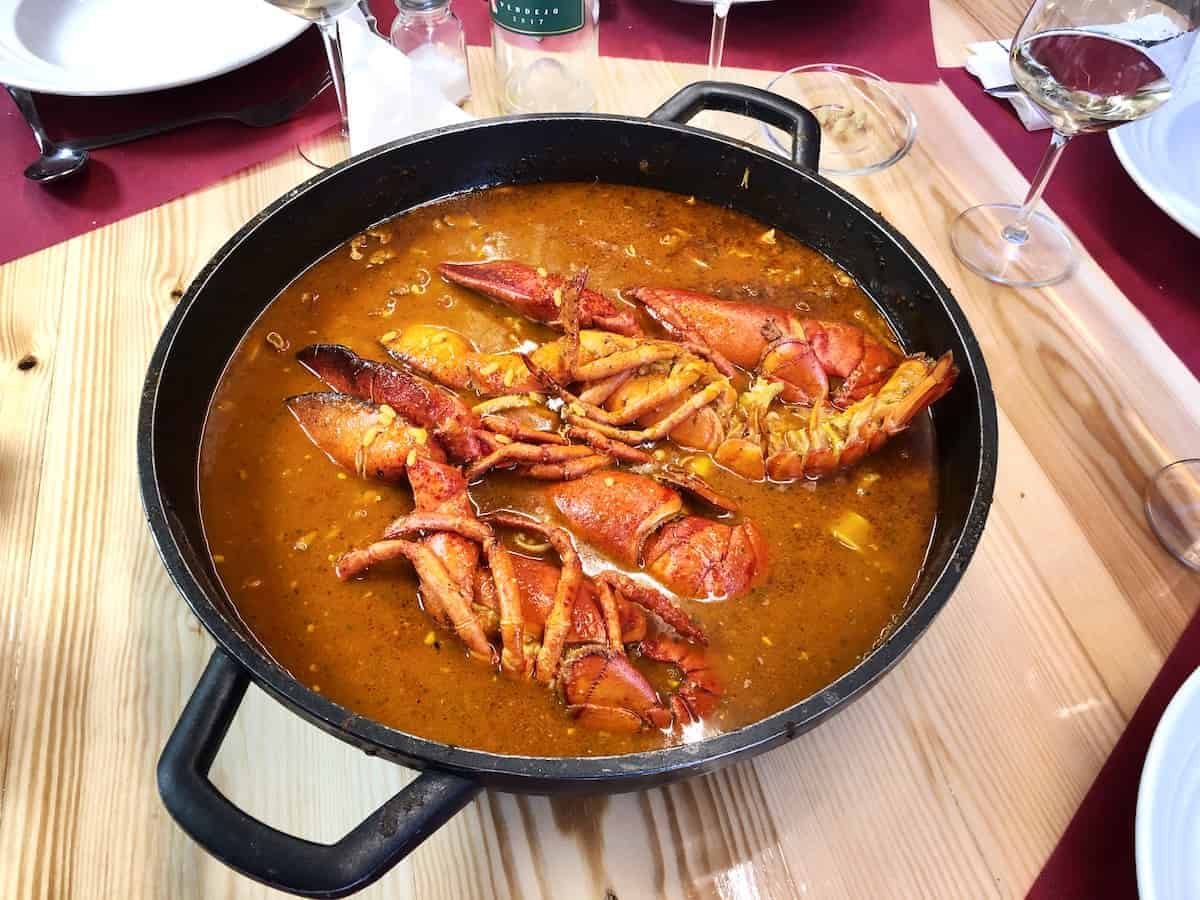 Large pot of soupy rice with lobster on a wooden tabletop.