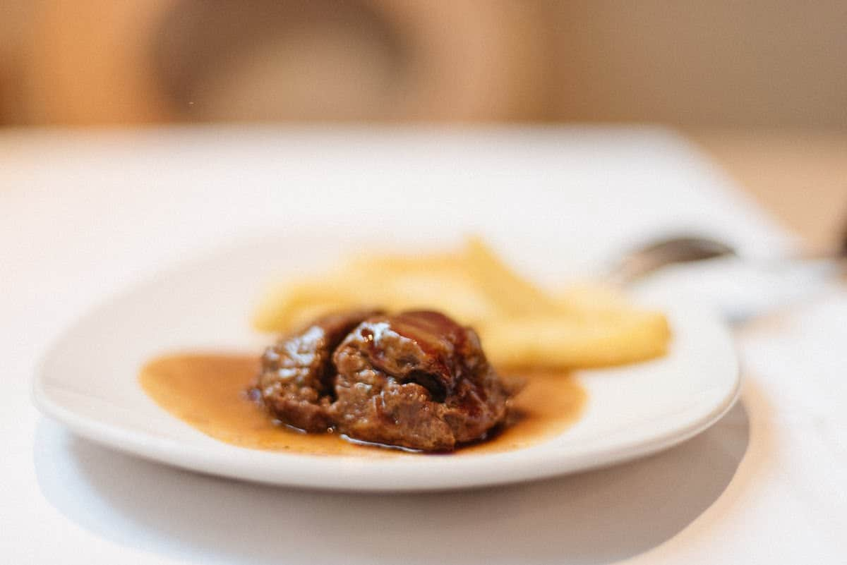Braised pork cheek in sauce next to french fries on a white plate.