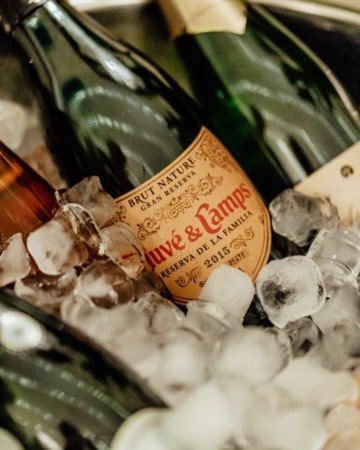 Close up of cava bottles chilling in a bucket of ice.