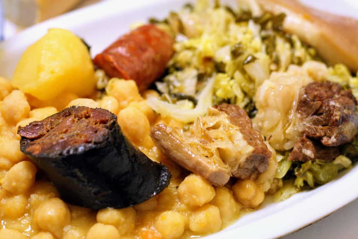 Stew of sausages, chickpeas, and vegetables on a white plate.