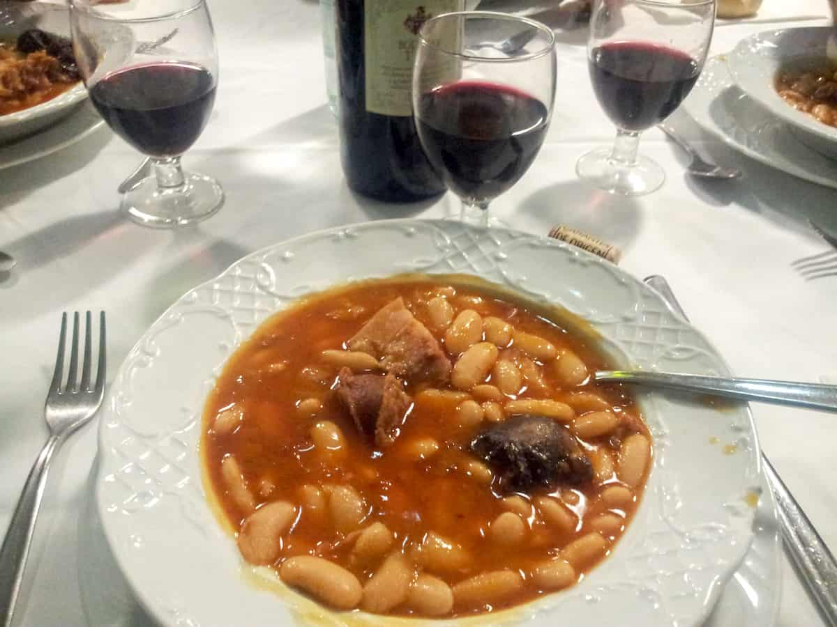 Bowl of white bean and sausage stew in front of three glasses of red wine.