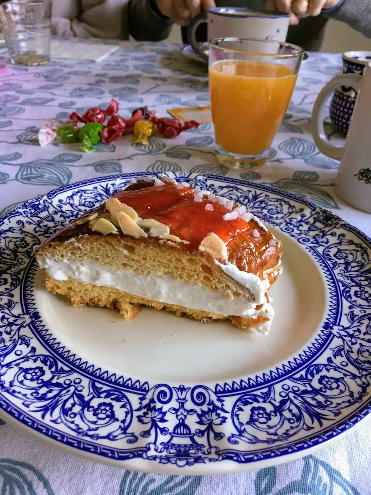 A cream-filled slice of Spanish king cake on a blue and white plate