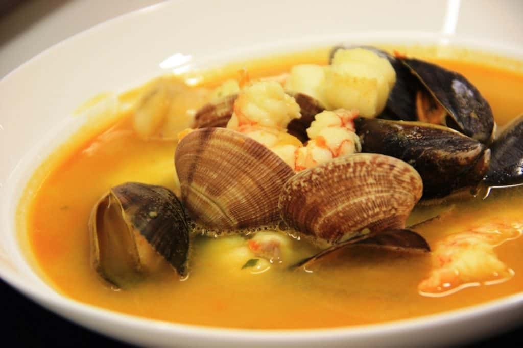 Close up of a bowl of seafood soup with clams, mussels, and shrimp.