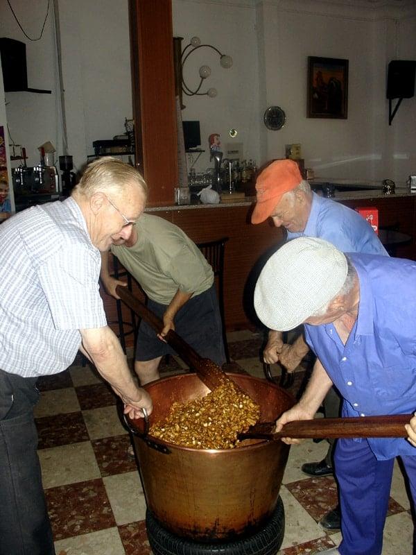 Four older men stir a huge vat of piñonate with wooden spoons