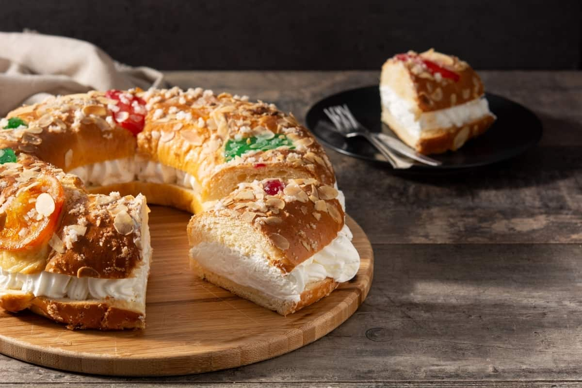 Roscon de Reyes stuffed with whipped cream on a counter with a plate with a slice behind it.