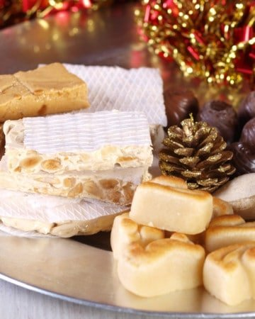 Turron and marzipan on a silver plate with pine cone decoration