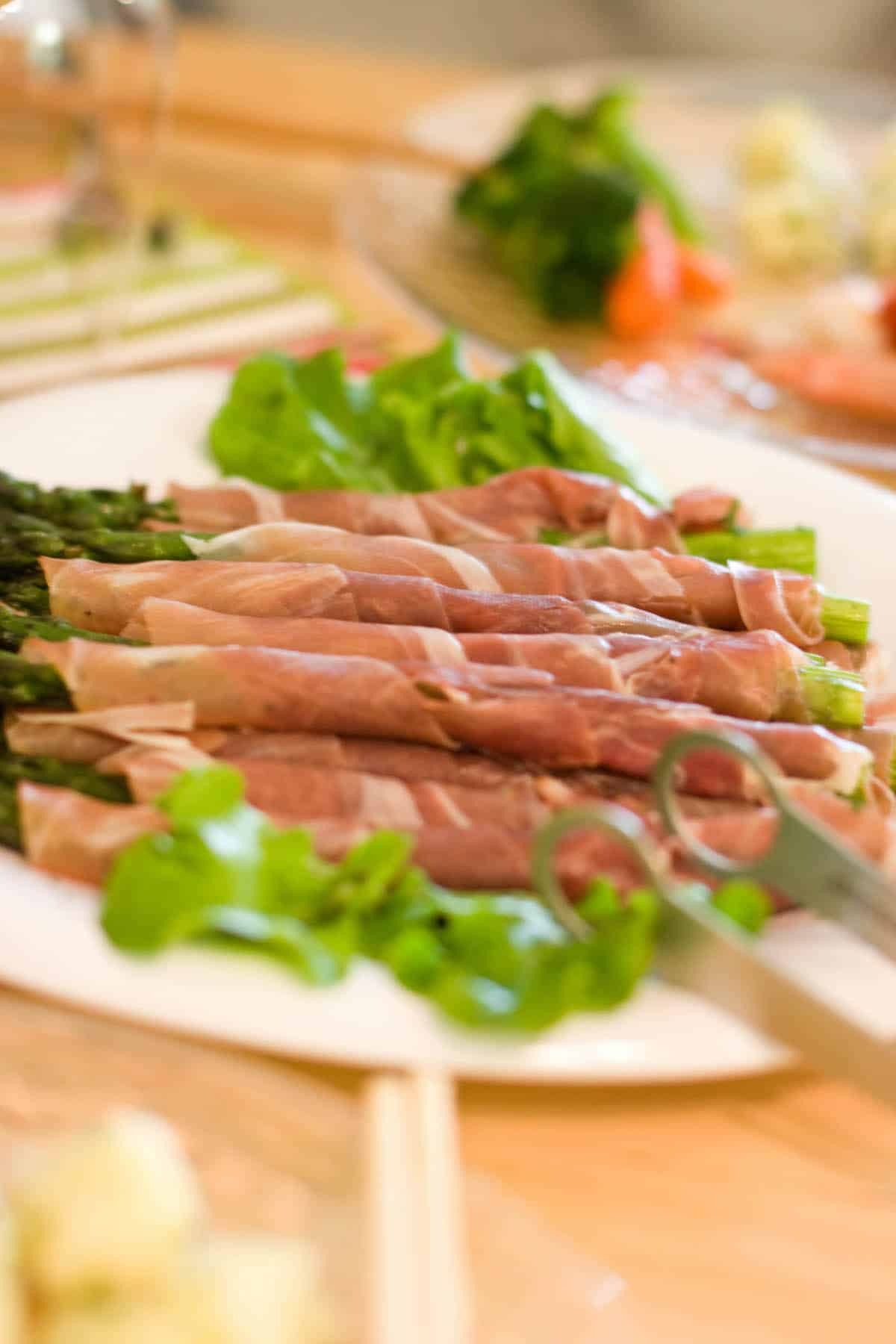 Green asparagus spears wrapped in slices of cured ham on a white plate