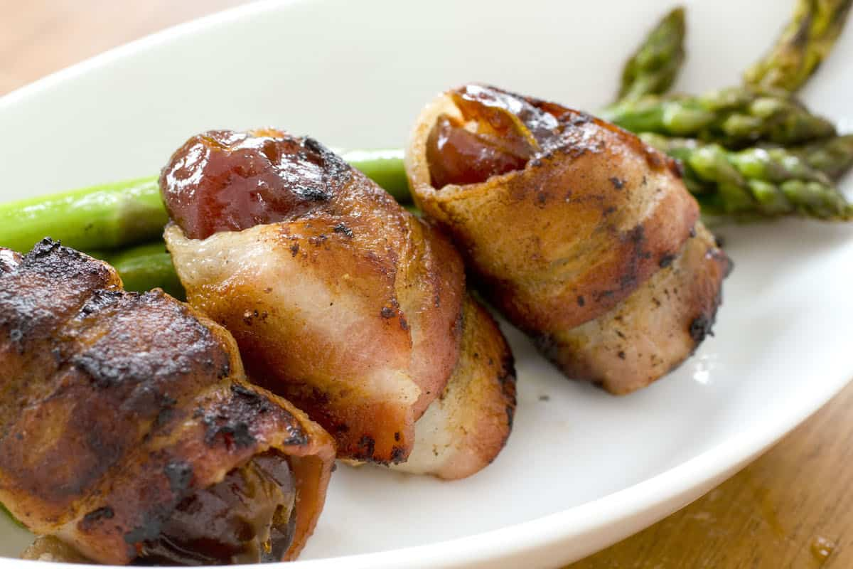 Three bacon-wrapped dates on a white plate in front of green asparagus