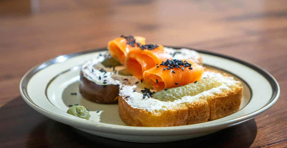 Slice of bread topped with cream cheese, smoked salmon, black sesame seeds, and pickles
