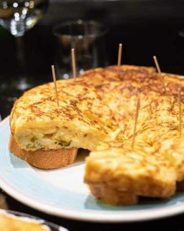 Slices of potato and pepper omelet served skewered atop pieces of bread