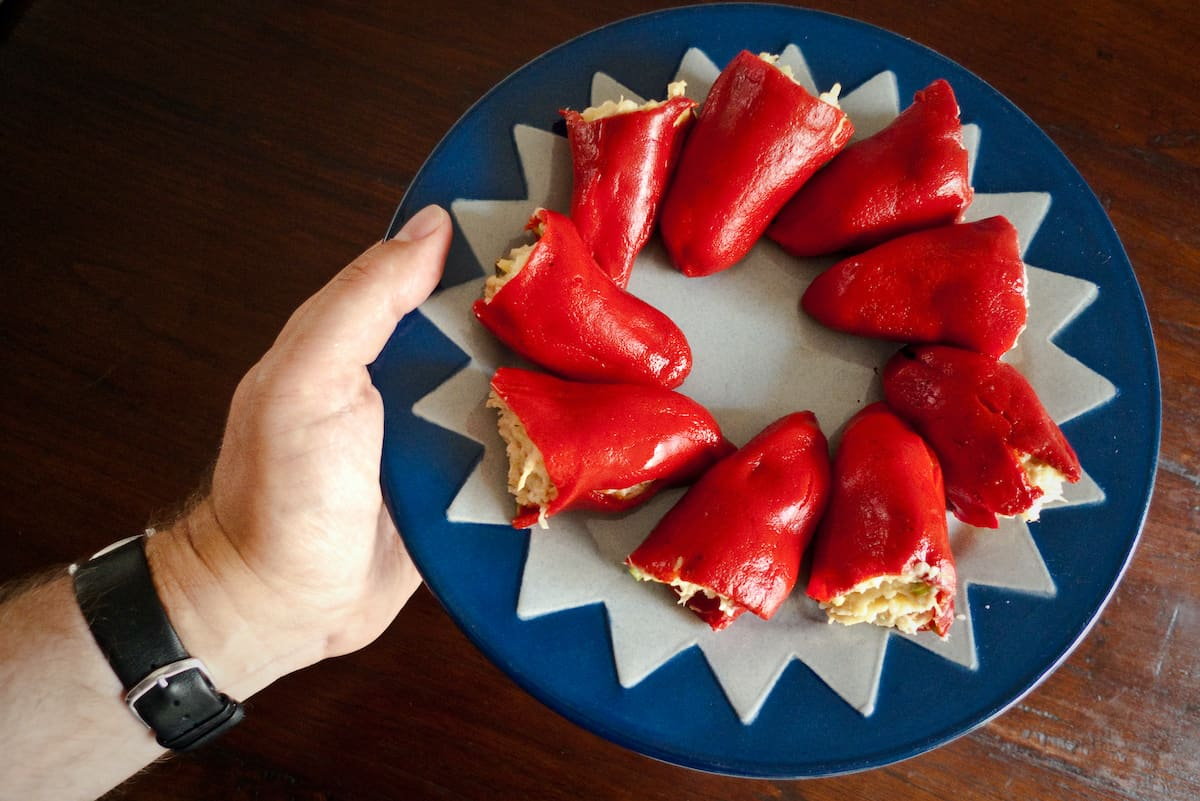 A person's hand holding a blue and white plate of red peppers stuffed with tuna