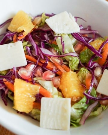 Winer salad with lettuce, cabbage carrot, pomegranate, orange and cheese in a white bowl.