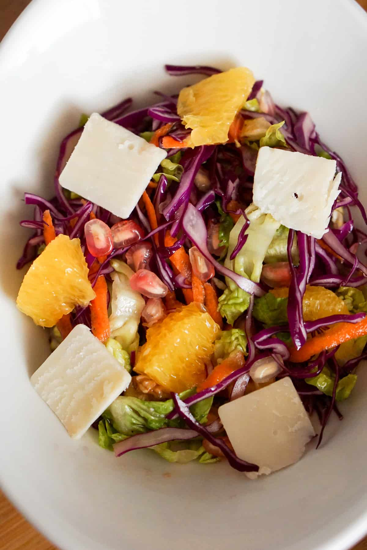 Winter salad in a white bowl: lettuce with shredded red cabbage and carrots, topped with cheese, orange slices and pomegranate seeds.