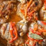 Chicken chilindron in a stainless steel skillet. An overhead photo of chicken thighs in a red sauce with onion and strips of bell pepper.