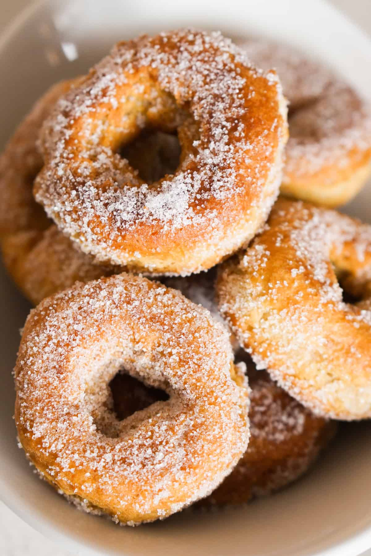 Sugar covered fried donuts in a white bowl.