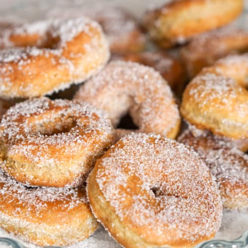 Sugar covered fried donuts in a glass dish.