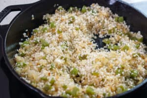 Rice, onion, and pepper in a cast iron pan.