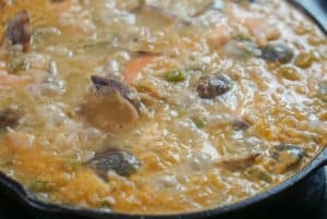 Adding the shellfish to the seafood rice dish in a cast iron pan