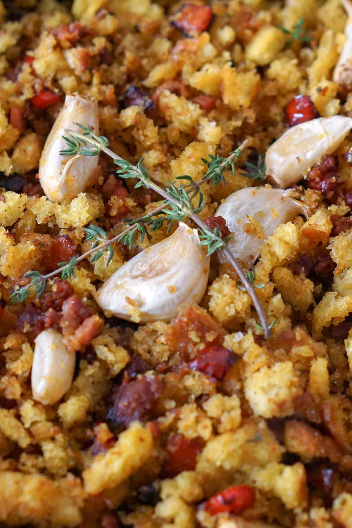 Vertical photo of migas con chorizo, golden fried bread crumbs with chorizo sausage and whole garlic cloves and rosemary on top.