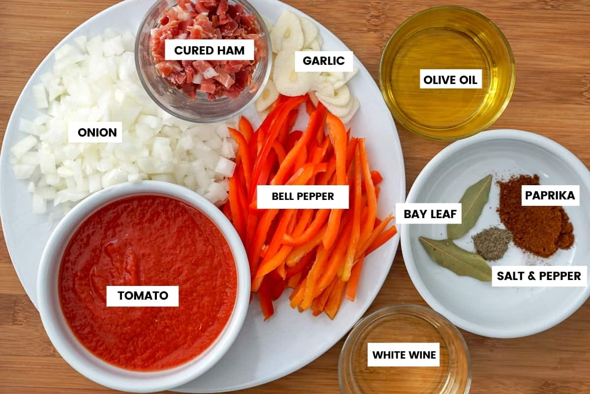Ingredients for chicken chilindron recipe: overhead photo with labels for diced onion, cured ham, sliced garlic, red bell pepper strips, tomato purée, olive oil, white wine, bay leaf, salt, pepper and paprika.