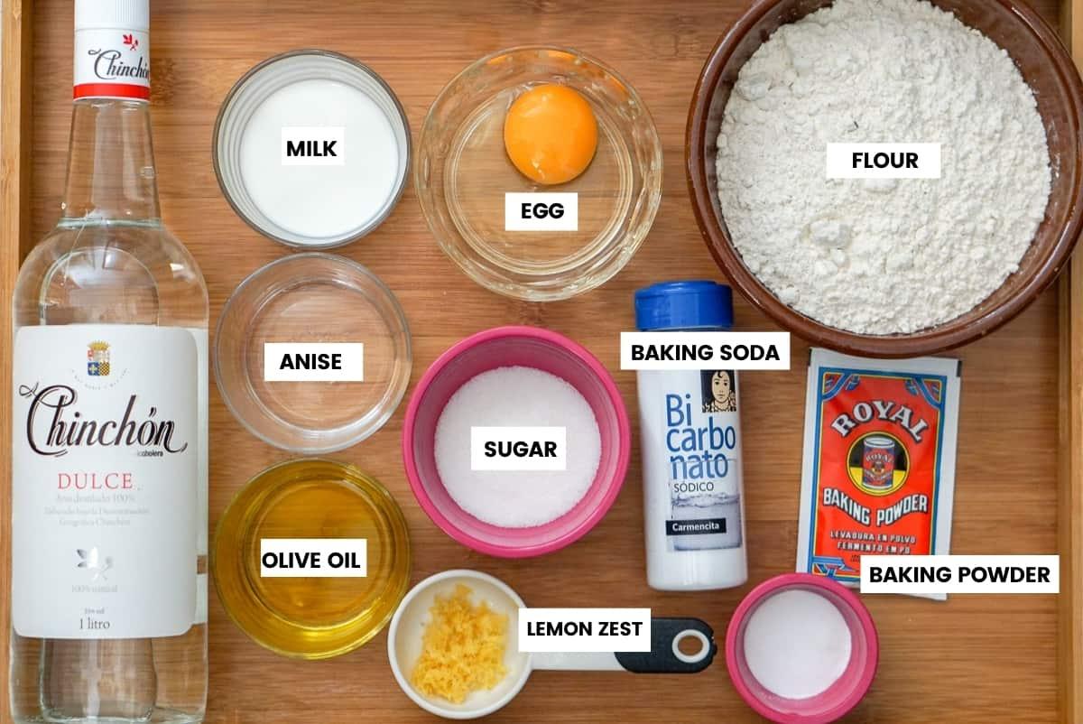 Ingredients for fried donuts on a wooden tray: sweet anise liquor, milk, egg, flour, sugar, baking soda, baking powder, olive oil, lemon zest