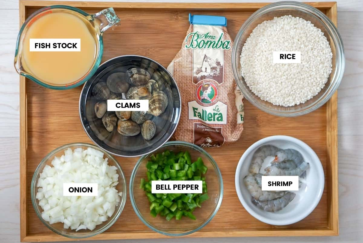 Ingredients for arroz caldoso on a brown tray. From the top left: fish stock, clams, rice, onion, bell pepper, and shrimp.