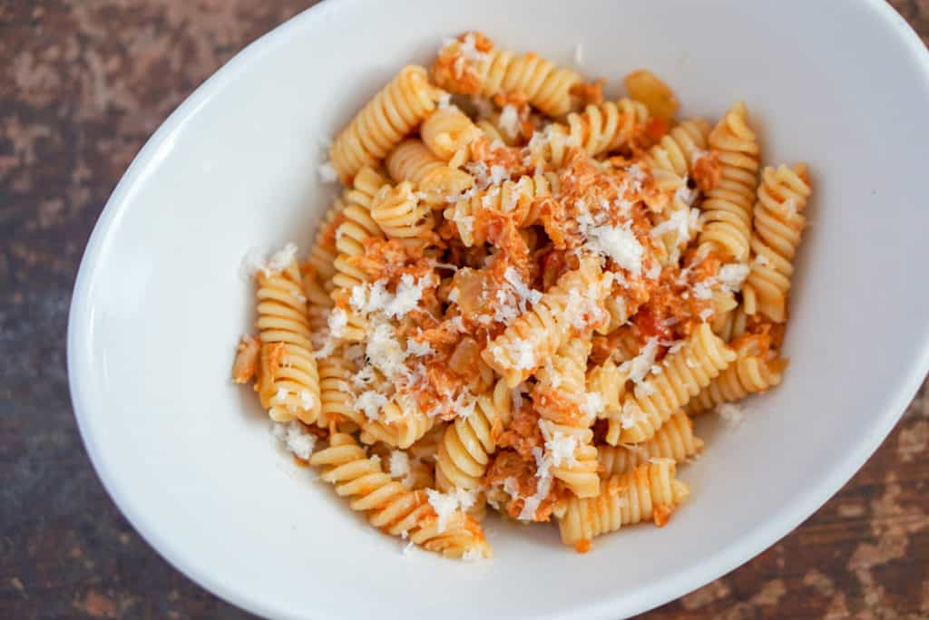 Tuna pasta with grated Manchego cheese in a white bowl.