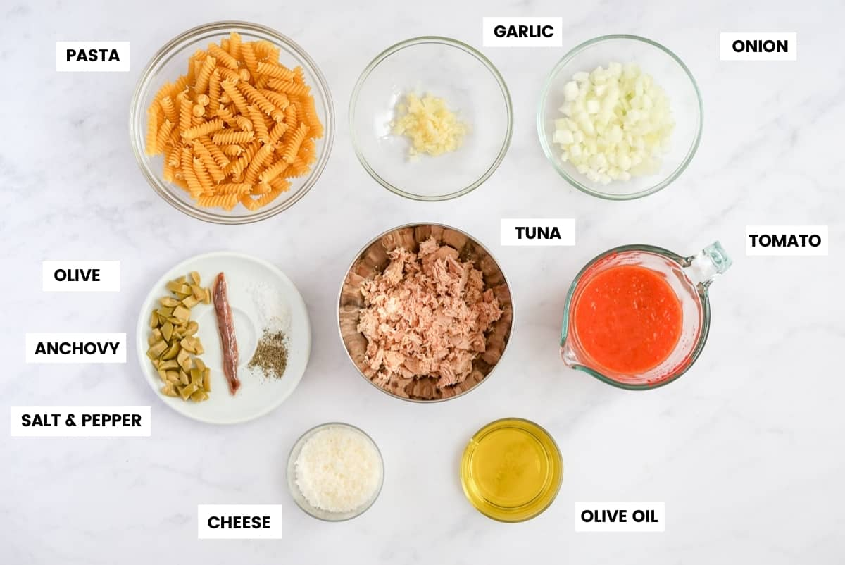 Tuna Pasta Ingredients overhead shot on a white background with labels: pasta in a clear bowl, minced garlic in a clear bowl, diced onion in a clear bowl, chopped olives, one anchovy, salt and pepper on a white plate, canned tuna in a metal bowl, crushed tomato in a glass measuring cup, grated cheese in a glass bowl and olive oil in a glass bowl