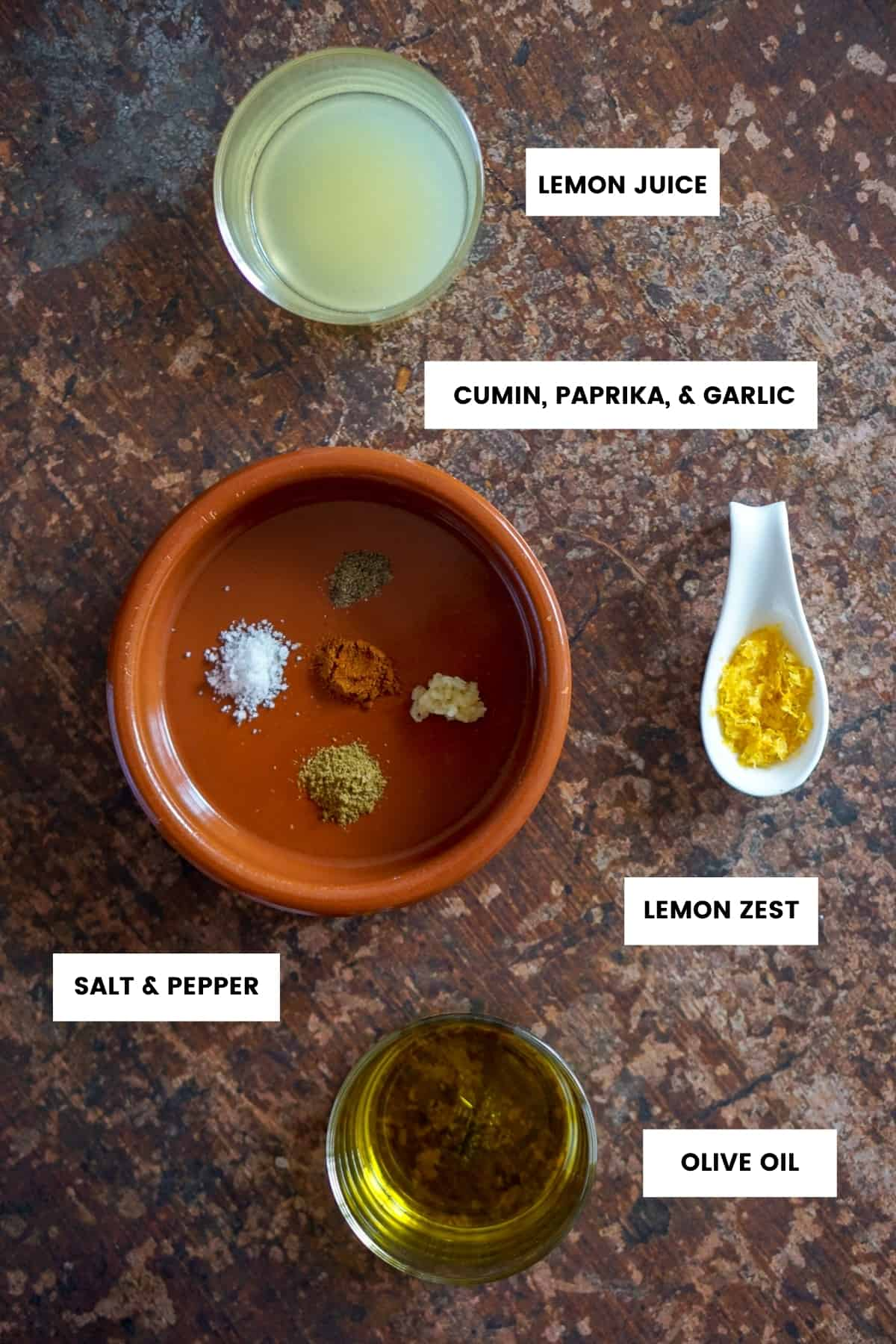 Lentil salad dressing ingredients with labels: lemon juice, lemon zest, salt, pepper, paprika, cumin, garlic, olive oil.