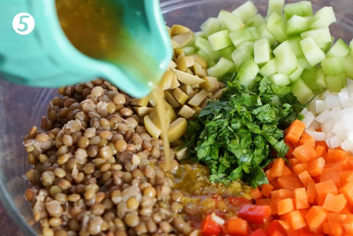 Lentil salad ingredients in a serving bowl and dressing being poured over.