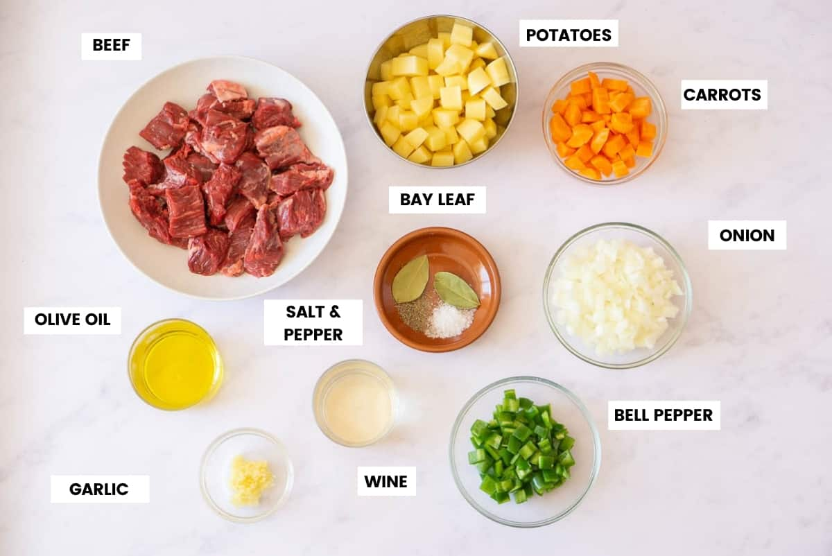 Ingredients for beef stew on a white marble background.