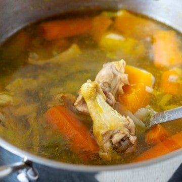 Pot of chicken stock with chicken and vegetables inside