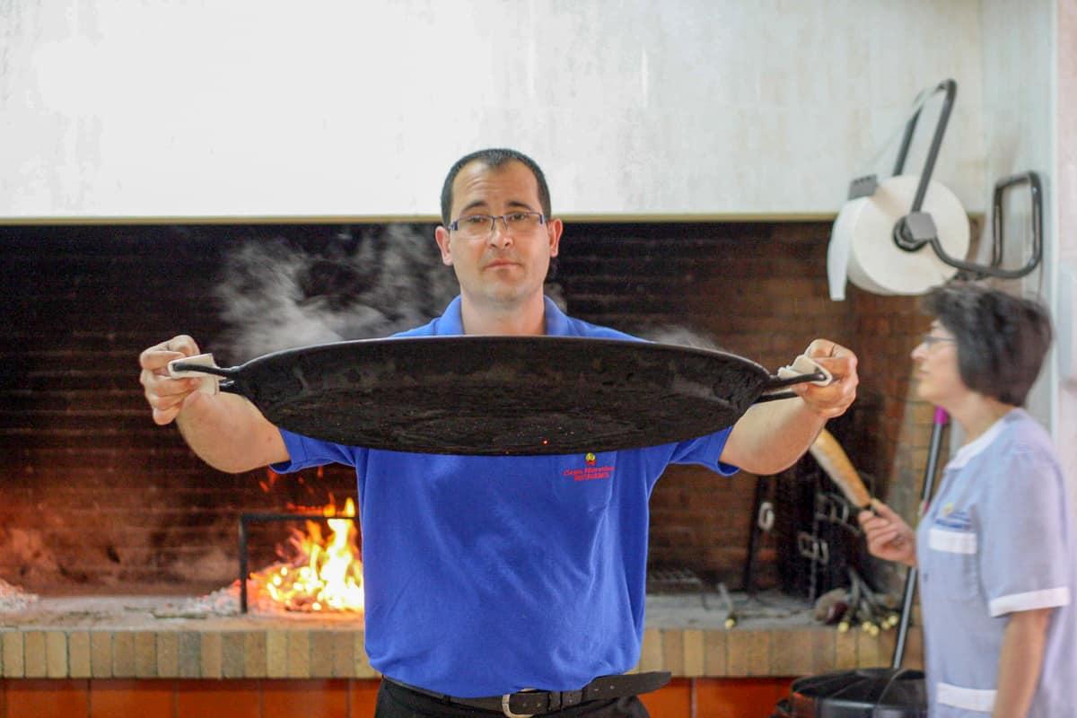 Man walking holding a large black paella pan