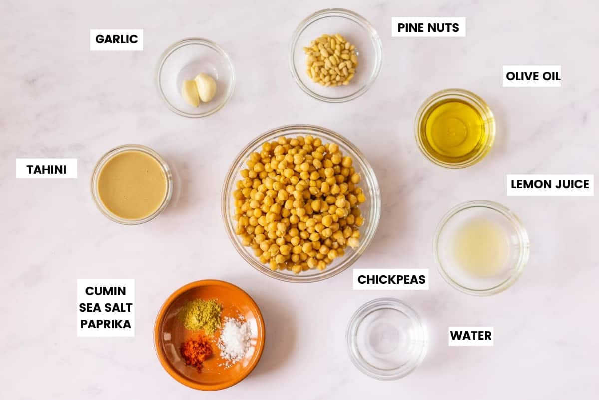 Ingredients to make Spanish hummus on a marble background with text overlay.