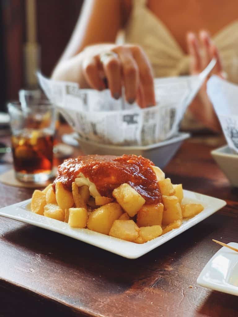 Plate of patatas bravas on a restaurant table with other dishes in the background.