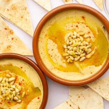 Two clay tapas dishes filled with hummus with pine nuts and paprika.