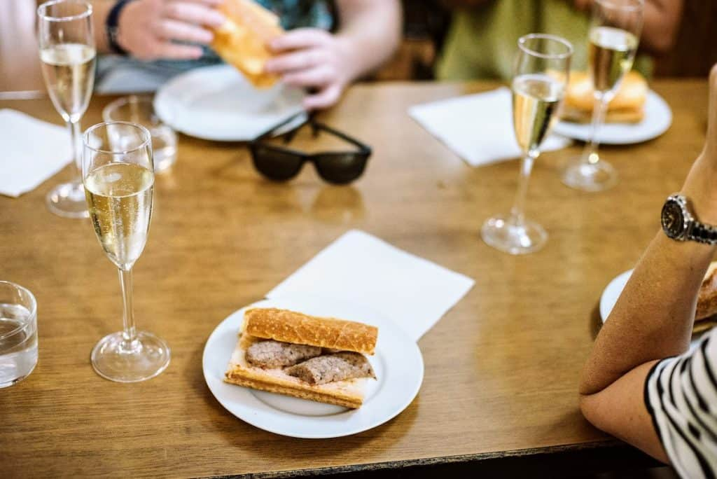 Slices of sausage in a bread roll on a white plate next to a glass of sparkling wine.