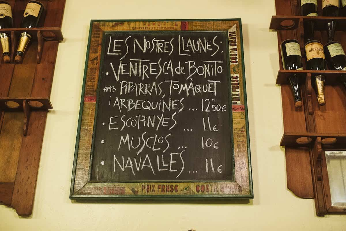 Chalkboard menu on a wall listing a restaurant's specialties in Catalan.
